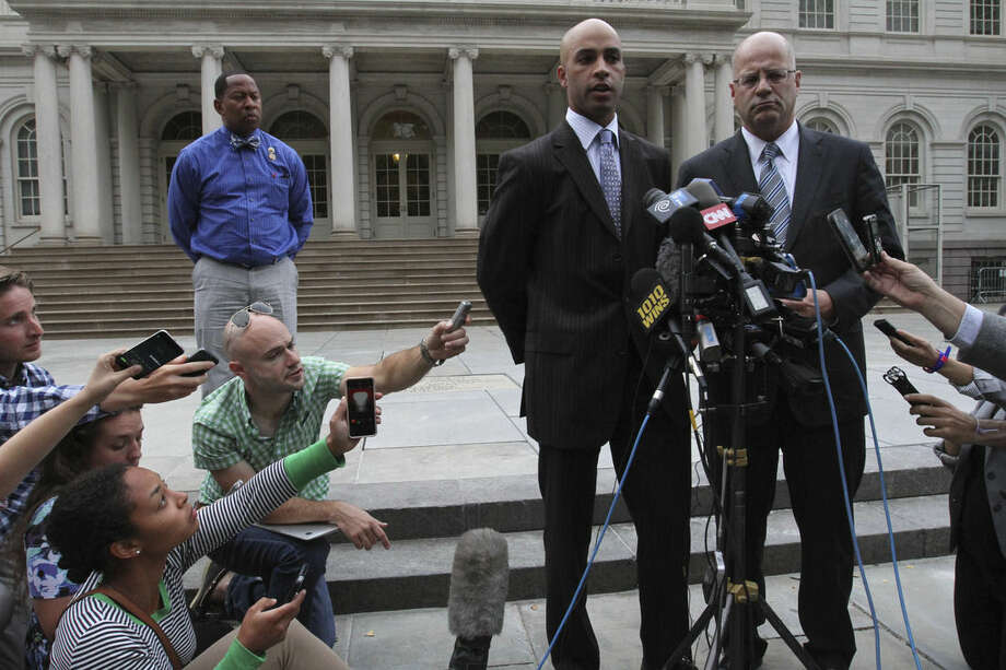 James Blake, second from right, talks to members of the media as his attorney Kevin H. Marino, right, looks on outside City Hall in New York after leaving the building Monday, Sept. 21, 2015. Blake, a former tennis star, was tackled during a mistaken arrest by a New York City police officer on Sept. 9. (AP Photo/Tina Fineberg)
