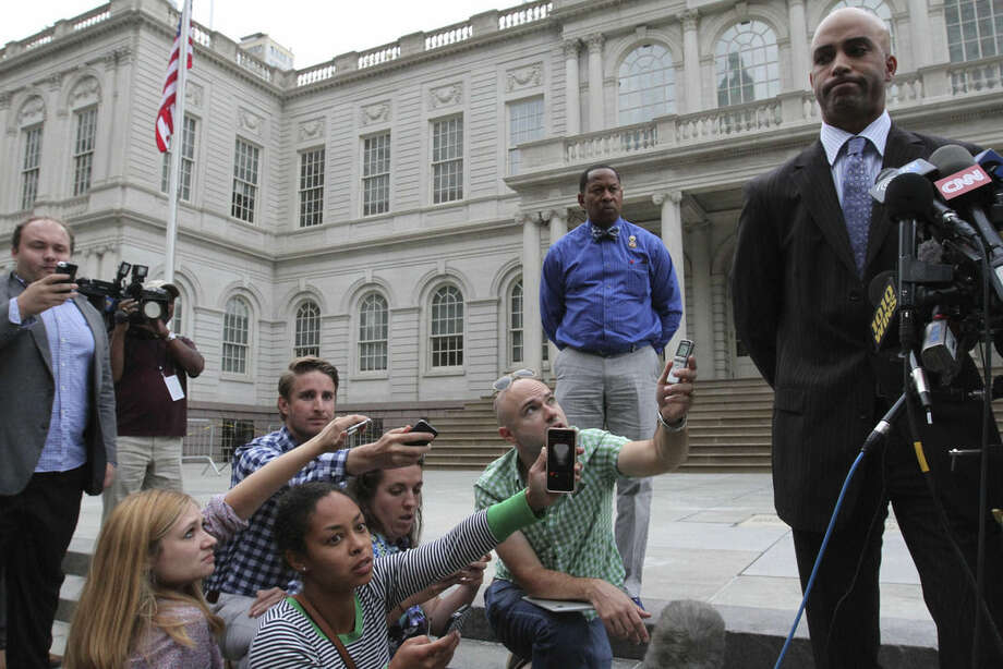 James Blake, right, talks to members of the media outside City Hall in New York after leaving the building Monday, Sept. 21, 2015. Blake, a former tennis star, was tackled during a mistaken arrest by a New York City police officer on Sept. 9. (AP Photo/Tina Fineberg)
