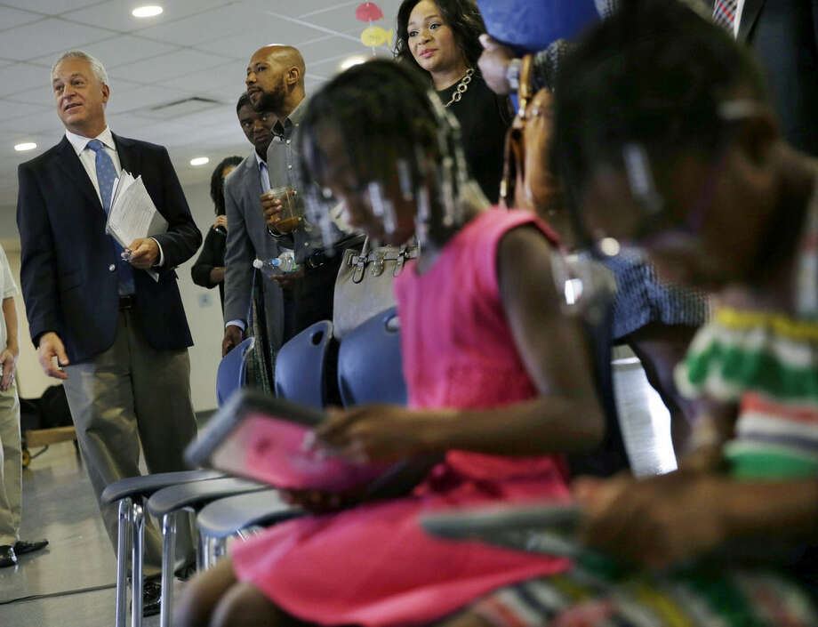 FILE - In this Wednesday, Sept. 2, 2015 file photo, young children use iPads as Newark public schools superintendent Christopher Cerf, left, listens to a question at First Avenue Elementary School in Newark, N.J. Cerf, the new superintendent of schools in Newark, appeared at the school to announce that district teachers would each receive $100 to spend as they wish on supplies and principals would get $7,500 for needs not covered in their budgets. The $750,000 for the program comes from the Foundation for Newark's Future, which was set up to distribute the $100 million donated five years ago by Facebook founder Mark Zuckerberg to improve education in Newark, a gift that has made the city a laboratory for educational changes. (AP Photo/Mel Evans, File)