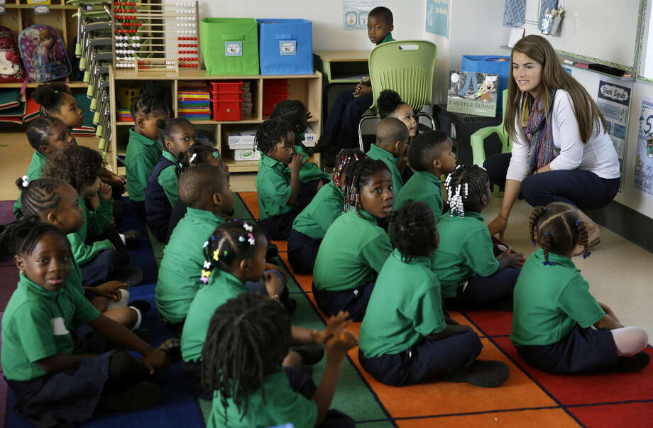Kindergarten teacher Liz Niehaus talks with her students at KIPP Thrive Academy, a new school in what had been the closed Eighteenth Avenue School, Wednesday, Sept. 9, 2015, in Newark, N.J. When Facebook founder Mark Zuckerberg appeared on Oprah Winfrey's show five years ago with a Democratic mayor and Republican governor to announce a $100 million donation to try to remake the education system in Newark, it was presented as an effort to make a struggling city into a national model for turning around urban schools systems. Thanks to Zuckerberg's money and another $100 million in matching donations, thousands of children have switched to publicly funded charter schools, where educational outcomes have generally been better for students. But the sped-up exodus has left traditional public schools in an ever-worsening financial condition and there's been no marked improvement in performance for the students left there; by several measures, there have been declines. (AP Photo/Mel Evans)