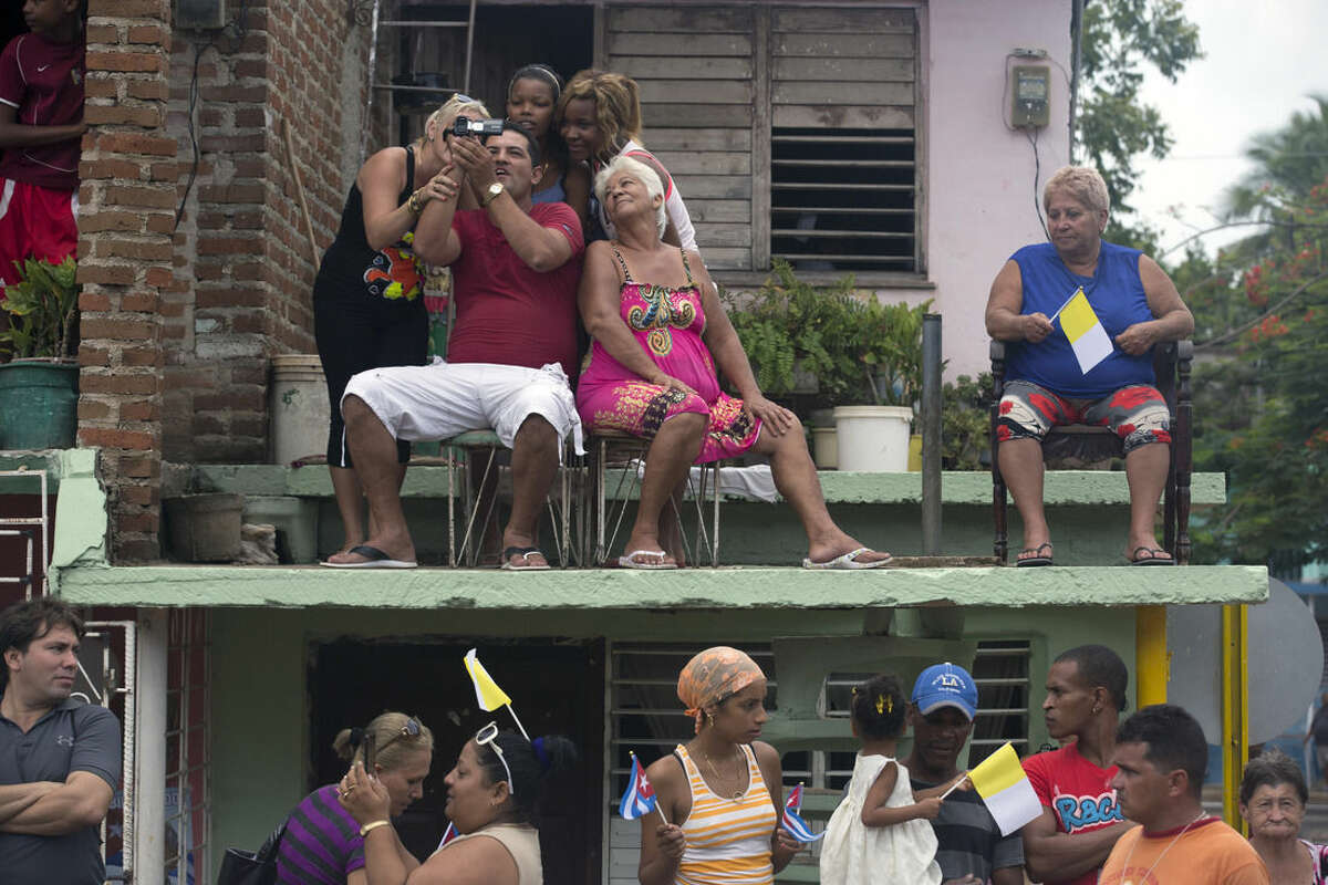 Residents wait for Pope Francis aboard his popemobile on the way to the Hill of the Cross in Holguin, Cuba, Monday, Sept. 21, 2015. Francis is ending his time in Holguin by blessing Cuba's fourth-largest city from the Hill of the Cross, a pilgrimage site overlooking the city. (AP Photo/Enric Marti)