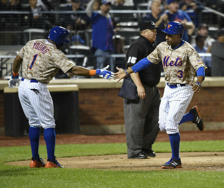 New York Mets' Eric Young Jr. (1) greets Curtis Granderson (3) at home plate after they both scored on Daniel Murphy's double off of Atlanta Braves relief pitcher Andrew McKirahan in the seventh inning of a baseball game, Monday, Sept. 21, 2015, in New York. (AP Photo/Kathy Kmonicek)