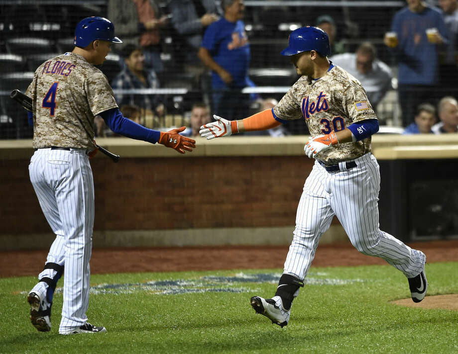 New York Mets' Wilmer Flores (4) greets teammate Michael Conforto (30) at home plate after Conforto hit a solo home run off of Atlanta Braves starting pitcher Shelby Miller in the second inning of a baseball game, Monday, Sept. 21, 2015, in New York. (AP Photo/Kathy Kmonicek)