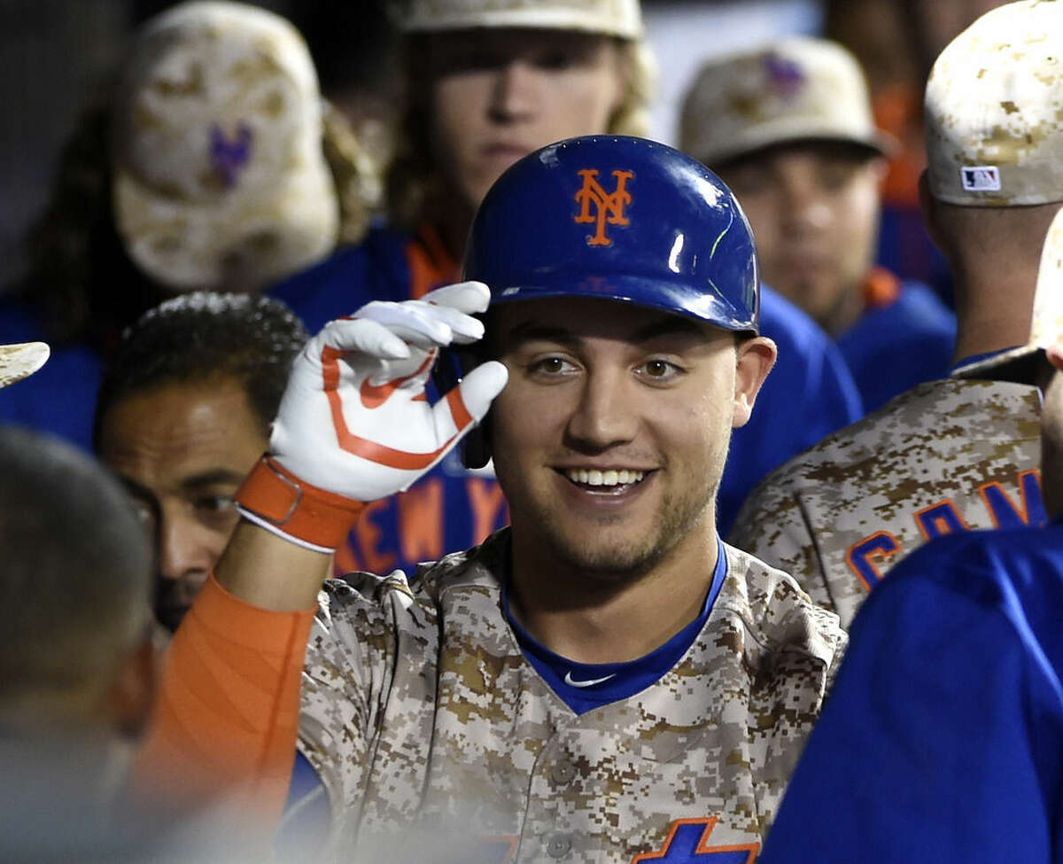 New York Mets' Michael Conforto celebrates his solo home run off Atlanta Braves starting pitcher Shelby Miller in the dugout with teammates in the second inning of a baseball game, Monday, Sept. 21, 2015, in New York. (AP Photo/Kathy Kmonicek)