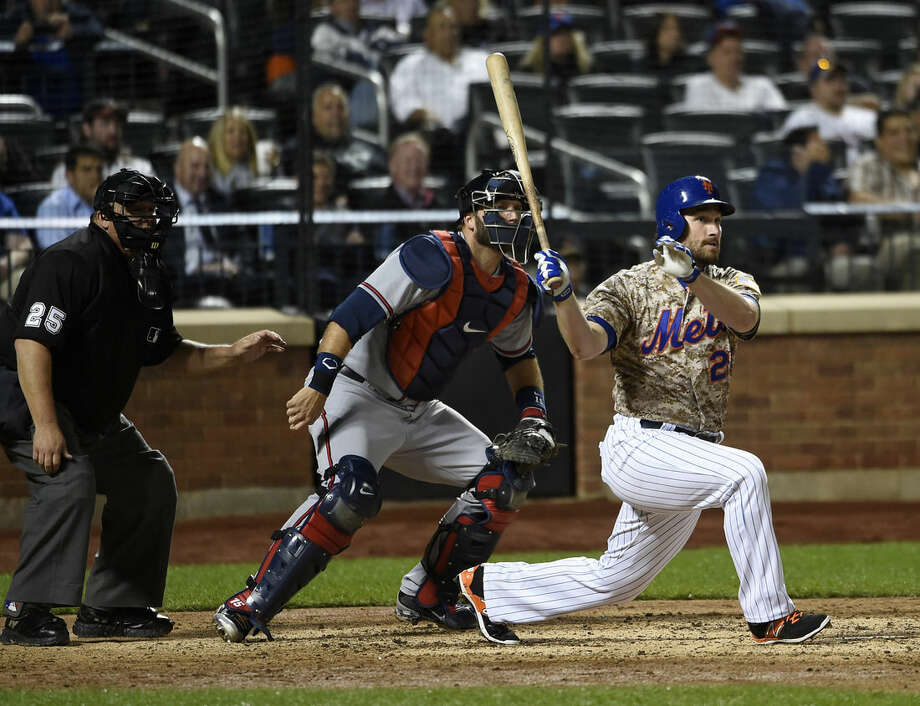 Atlanta Braves catcher A.J. Pierzynski, center, and New York Mets' Daniel Murphy, right, watch Murphy's two-run double in the seventh inning of a baseball game, Monday, Sept. 21, 2015, in New York. (AP Photo/Kathy Kmonicek)