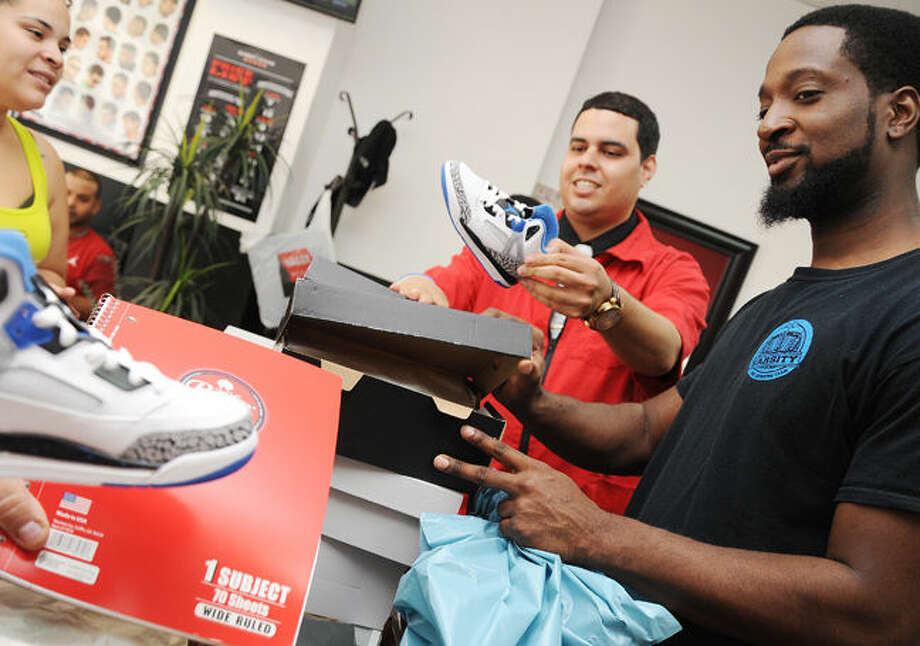 Joel Figueroa owner of Joel's Barber Lounge with his back to school drive partner Jean Gabriel break out new sneakers for the raffle winners to get for their first day of school. Hour photo/Matthew Vinci