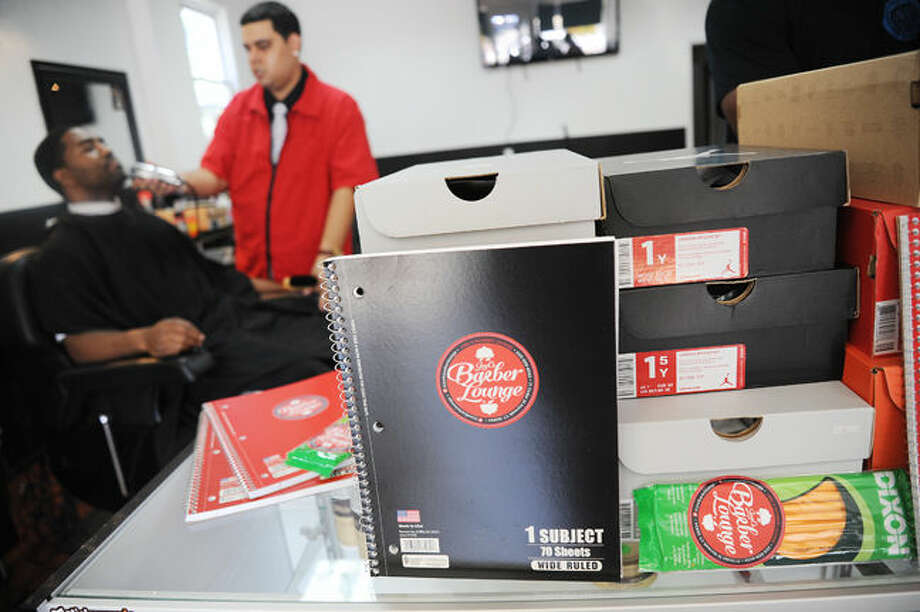Back to school supplies donated for kids Sunday at Joel's Barber Lounge. Kids got a backpack a note book and pencils, some lucky raffle winners got a new pair sneakers was well. Hour photo/Matthew Vinci