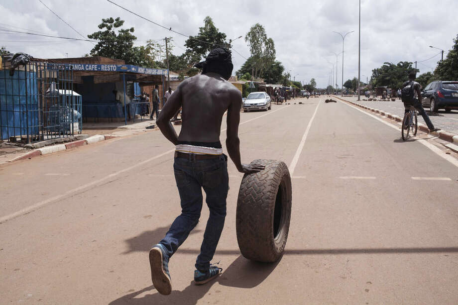 A protestor rolls a tire down the road to be burnt as part of their protest against the recent coup in Ouagadougou, Burkina Faso, Tuesday, Sept. 22, 2015. The leader of a coup in Burkina Faso on Tuesday refused to heed a deadline for his men to return to barracks even after troops opposing the takeover poured into the capital. (AP Photo/Theo Renaut)