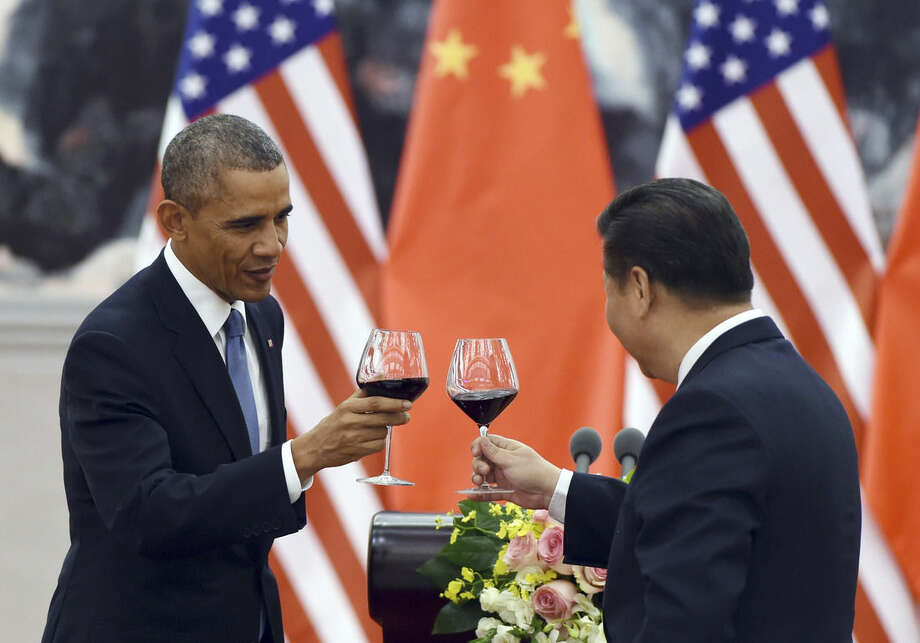 FILE - In this Nov. 12, 2014, file photo, President Barack Obama toasts with Chinese President Xi Jinping at a lunch banquet in the Great Hall of the People in Beijing. There could be some awkward undercurrents when the Chinese president is honored with a state dinner at the White House on Friday. The Obama's will honor a guest whose country has been accused of cyberspying, trampling on human rights and engaging in assertive military tactics. (AP Photo/Greg Baker, File-Pool)