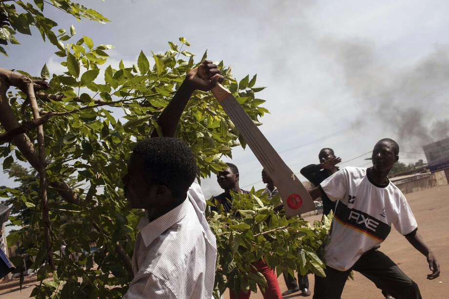 A protester cuts a branch to be burnt, as he and others demonstrate against the recent coup by burning a tires and making makeshift road blocks in Ouagadougou, Burkina Faso, Tuesday, Sept. 22, 2015. The leader of a coup in Burkina Faso on Tuesday refused to heed a deadline for his men to return to barracks even after troops opposing the takeover poured into the capital. (AP Photo/Theo Renaut)