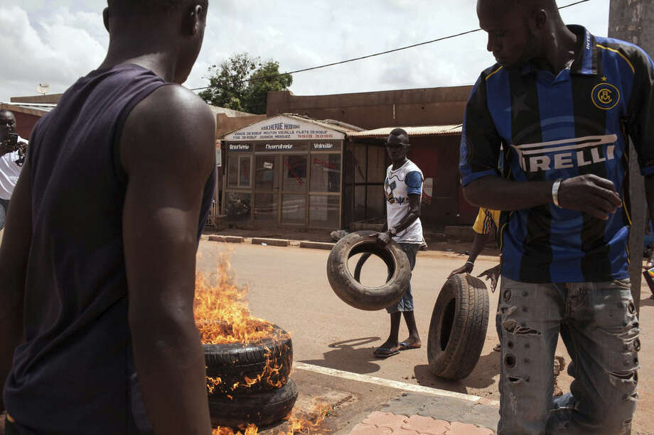 People demonstrating against the recent coup burn tires and make makeshift road blocks in Ouagadougou, Burkina Faso, Tuesday, Sept. 22, 2015. The leader of a coup in Burkina Faso on Tuesday refused to heed a deadline for his men to return to barracks even after troops opposing the takeover poured into the capital. (AP Photo/Theo Renaut)