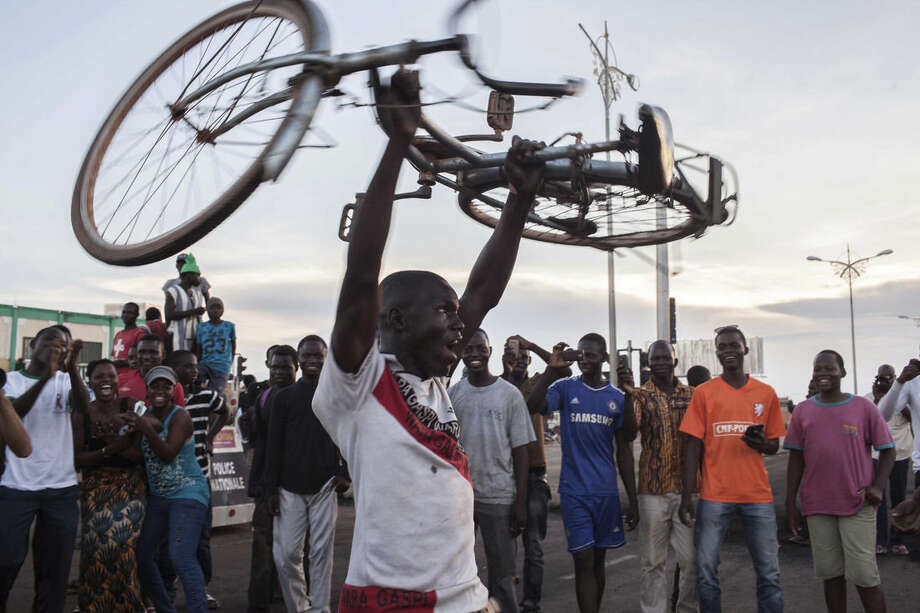 In this photo taken Monday, Sept. 21, 2015, a protestor holds a bike in the air as he and others protest against a recent coup in Ouagadougou, Burkina Faso. Demonstrators took to the streets of Burkina Faso's capital Monday, burning tires to protest a proposed compromise solution to the country's deepening political crisis as tensions mounted over military rule. Regional mediators spent the weekend trying to broker a compromise between the junta that seized power in a coup last week and other politicians in this West African country. They announced a plan late Sunday that calls for new elections by the end of November. (AP Photo/Theo Renaut)