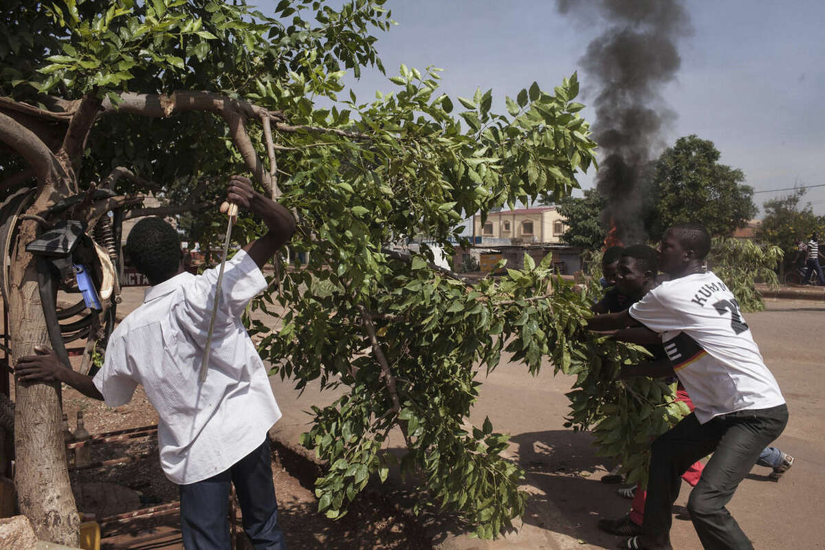 A protester, left, cuts a branch to be burnt as he and others demonstrate against the recent coup by burning a tires and making makeshift road blocks in Ouagadougou, Burkina Faso, Tuesday, Sept. 22, 2015. The leader of a coup in Burkina Faso on Tuesday refused to heed a deadline for his men to return to barracks even after troops opposing the takeover poured into the capital. (AP Photo/Theo Renaut)