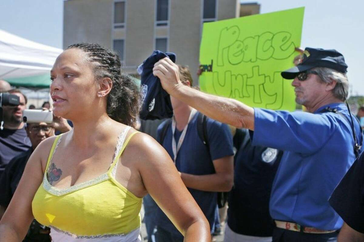 Sondra Fifer, of St. Louis, voices her disagreement with the rally for Ferguson police Officer Darren Wilson on Saturday, Aug. 23, 2014, at Barney's Sports Pub in St. Louis.