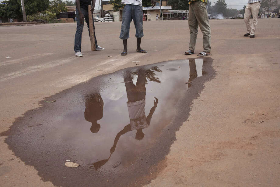 The refection of people demonstrating against the recent coup by burning tires and making makeshift road blocks is seen in a puddle in Ouagadougou, Burkina Faso, Tuesday, Sept. 22, 2015. The leader of a coup in Burkina Faso on Tuesday refused to heed a deadline for his men to return to barracks even after troops opposing the takeover poured into the capital. (AP Photo/Theo Renaut)