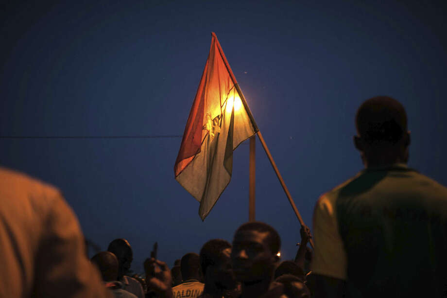 In this photo taken Monday, Sept. 21, 2015, a protestor holds a Burkina Faso national flag during a protest against a recent coup in Ouagadougou, Burkina Faso. Demonstrators took to the streets of Burkina Faso's capital Monday, burning tires to protest a proposed compromise solution to the country's deepening political crisis as tensions mounted over military rule. Regional mediators spent the weekend trying to broker a compromise between the junta that seized power in a coup last week and other politicians in this West African country. They announced a plan late Sunday that calls for new elections by the end of November. (AP Photo/Theo Renaut)