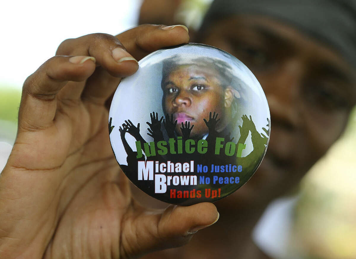 FILE - In this Aug. 21, 2014 file photo, Nikki Jones, of Spanish Lake, Mo, holds a button in support of Michael Brown while visiting the community in the apartment development near where he was fatally shot in Ferguson, Mo. After Brown's Aug. 9 shooting death at the hands of a white police officer his legacy continues to evolve. (AP Photo/Atlanta Journal Constitution, Curtis Compton, File)