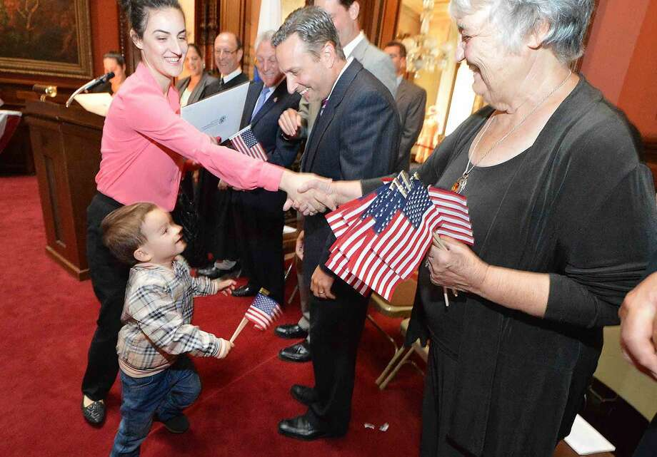 Hour Photo/Alex von Kleydorff 3yr old Aron runs up to his mom Mema Besmira as she accepts her Naturalization certificate from U.S. Magistrate Judge The Hon. William Garfinkel and is greeted by State Sen. Bob Duff, Norwalk Mayor Harry Rilling and Congressman Jim Himes, and gets a flag and a handshake from Lockwood Matthews Mansion Museum Chairman of the Board of Trustees Patsy Brescia.