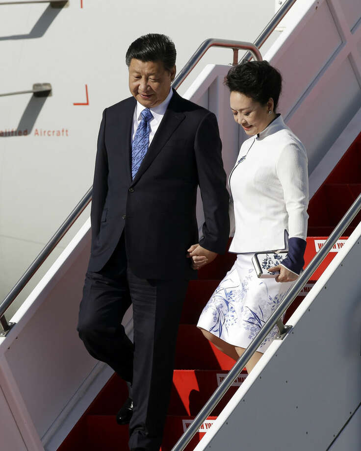 Chinese President Xi Jinping, left, and his wife Peng Liyuan exit their aircraft upon arriving Tuesday, Sept. 22, 2015, at Boeing Field in Everett, Wash. Xi is spending three days in Seattle before traveling to Washington, D.C., for a White House state dinner on Friday. (AP Photo/Elaine Thompson)