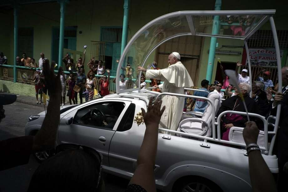 """People wave to Pope Francis as he leaves the Metropolitan Cathedral, in route to the airport in Santiago de Cuba, Cuba, Tuesday, Sept. 22, 2015. Pope Francis on Tuesday called on Cubans to rediscover their Catholic heritage and live a """"revolution of tenderness,"""" powerful words in a country whose 1959 revolution installed an atheist, communist government that sought to replace the church as the guiding force in people's lives. (AP Photo/Ramon Espinosa)"""