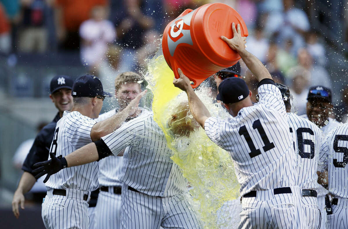 New York Yankees' Brett Gardner (11) douses teammate Brian McCann after McCann hit a baseball game-winning three-run home run off Chicago White Sox relief pitcher Jake Petricka in the 10th inning at Yankee Stadium in New York, Sunday, Aug. 24, 2014. (AP Photo/Kathy Willens)
