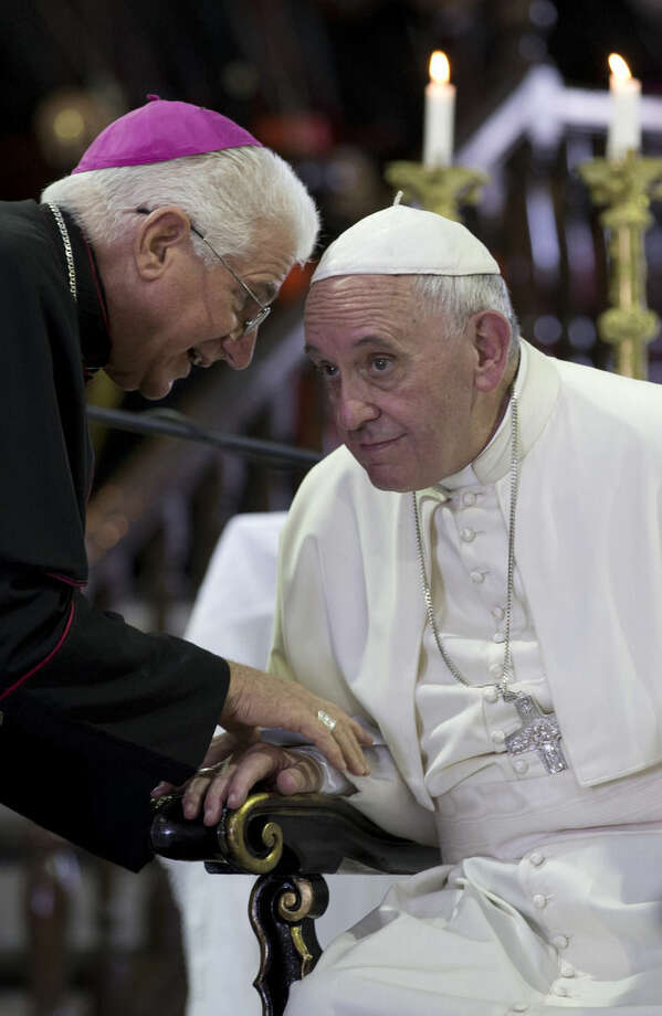 """Pope Francis listens to Bishop of Santiago de Cuba Dionisio Guillermo Garcia Ibanez during Mass at the sanctuary of the Virgin of Charity in El Cobre, Cuba, Tuesday, Sept. 22, 2015. Pope Francis on Tuesday called on Cubans to rediscover their Catholic heritage and live a """"revolution of tenderness,"""" powerful words in a country whose 1959 revolution installed an atheist, communist government that sought to replace the church as the guiding force in people's lives. (Ismael Francisco/Cubadebate via AP)"""
