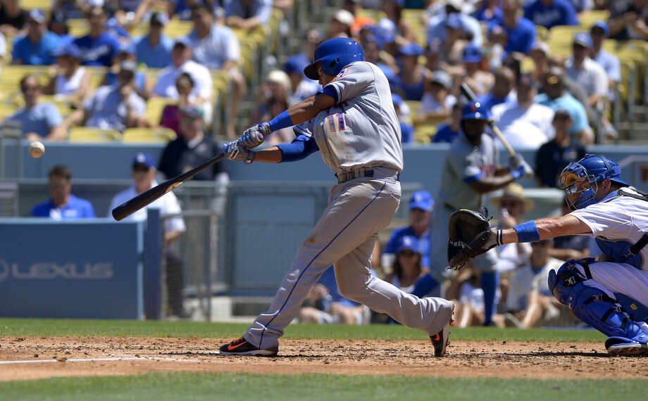 New York Mets' Ruben Tejada, left, hits a two-run home run as Los Angeles Dodgers catcher A.J. Ellis, right, looks on during the third inning of a baseball game, Sunday, Aug. 24, 2014, in Los Angeles. (AP Photo/Mark J. Terrill)