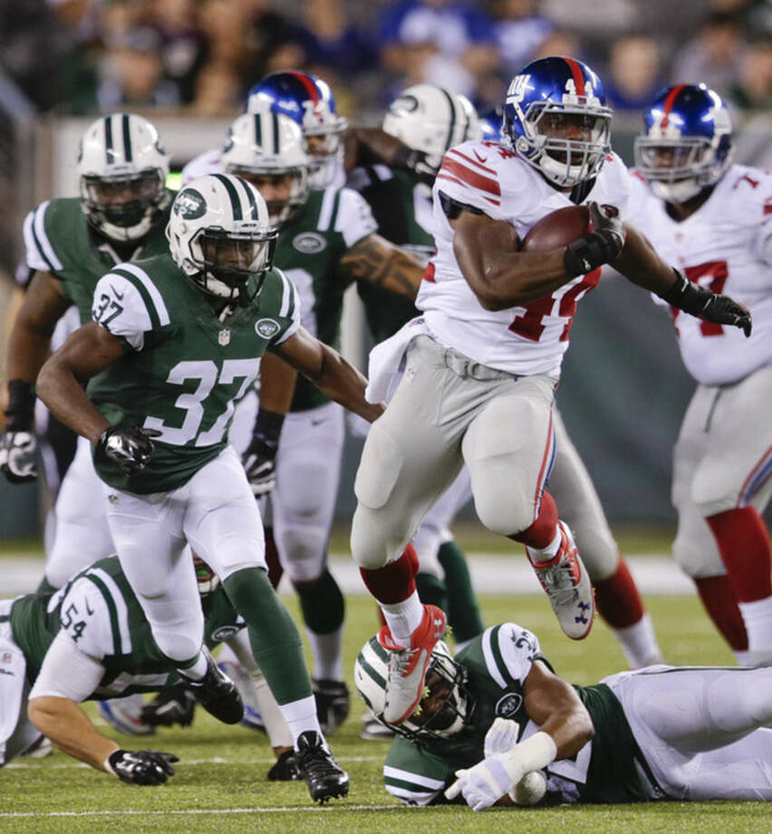 New York Giants running back Andre Williams (44) gets past the New York Jets defense in the fourth quarter of a preseason NFL football game, Friday, Aug. 22, 2014, in East Rutherford, N.J. (AP Photo/Julio Cortez)