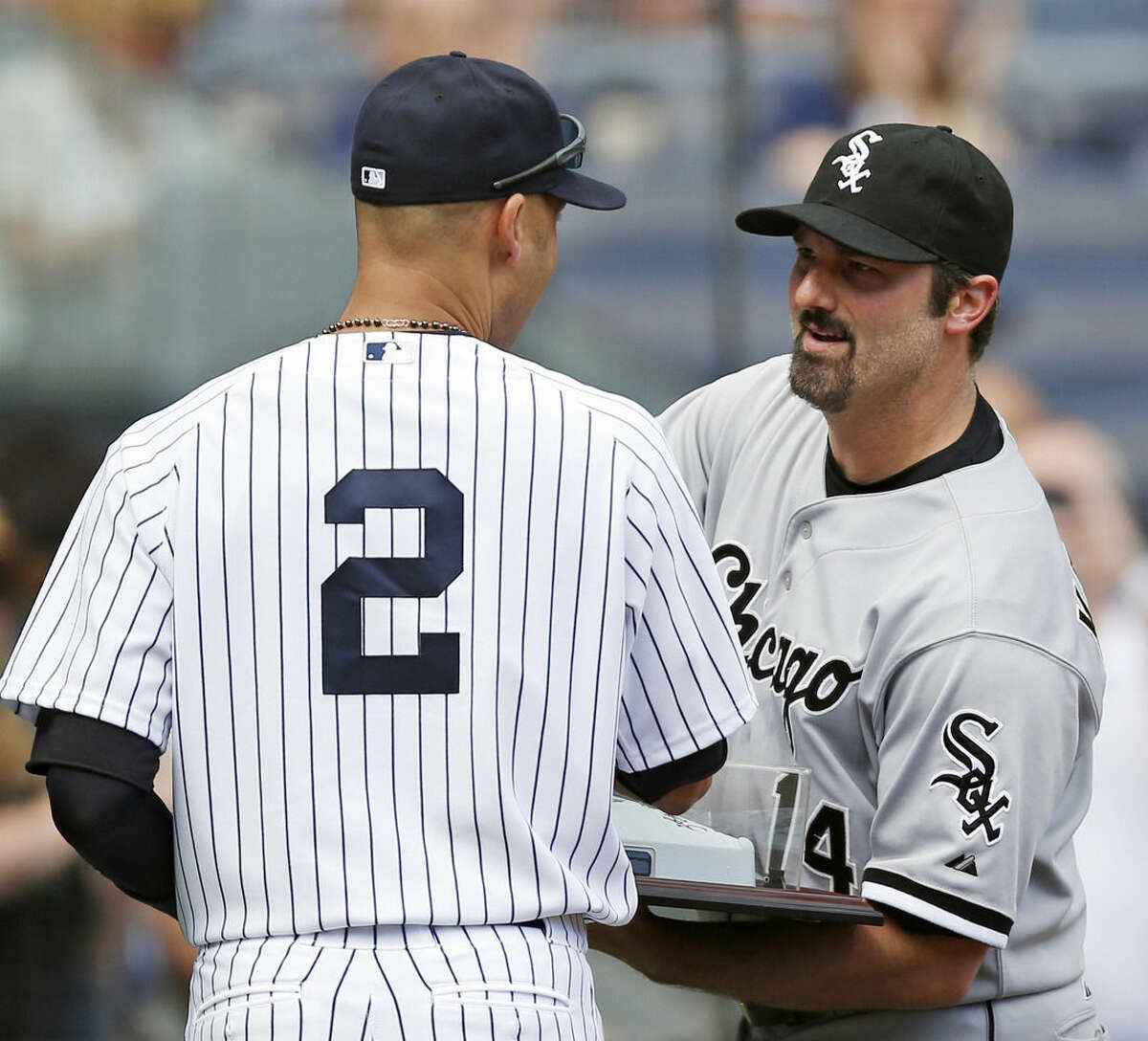 Chicago White Sox designated hitter Paul Konerko accepts an autographed base from New York Yankees shortstop Derek Jeter (2) before their two teams face each other in a baseball game at Yankee Stadium in New York, Sunday, Aug. 24, 2014. (AP Photo/Kathy Willens)