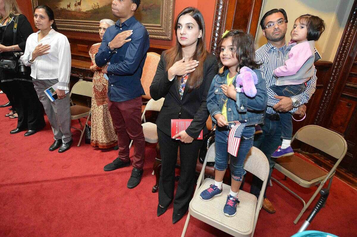 Hour Photo/Alex von Kleydorff Munaza Malik from Pakistan becomes a naturalized U.S. citizen while Aziz Sheikh and daughters 5yr old Alaina and 3yr old Emaan place hands on their hearts as The Pledge of Allegiance is read during a special Naturalization ceremony held at Norwalk's Lockwood Matthews Mansion Museum on Tuesday