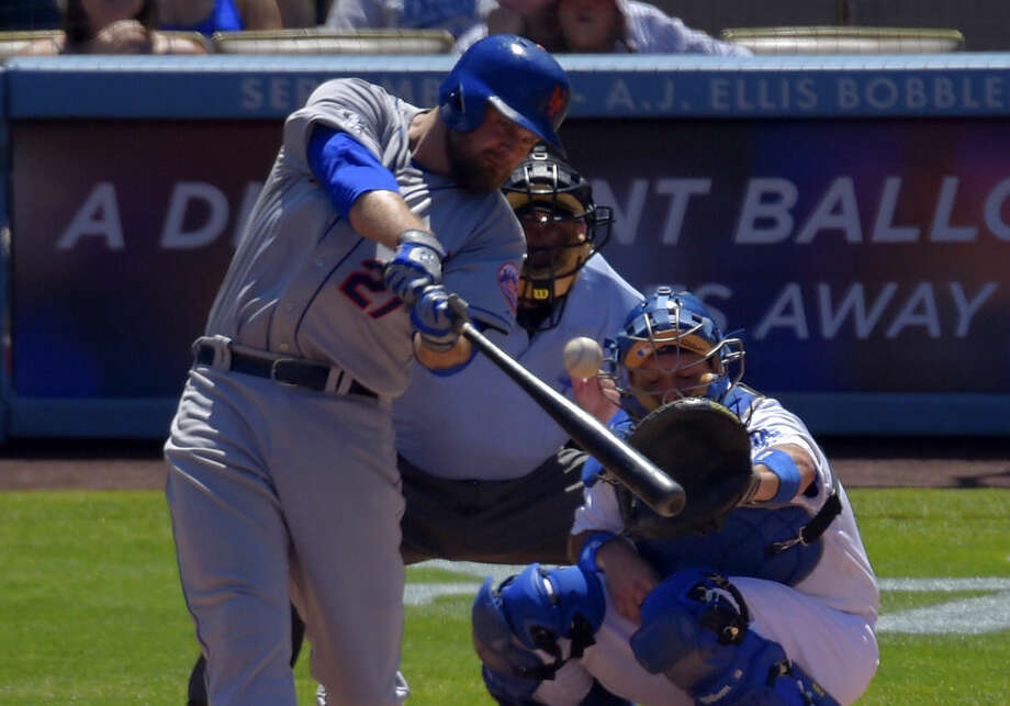 New York Mets' Lucas Duda, left, hits a three-run home run as Los Angeles Dodgers catcher A.J. Ellis, right, and home plate umpire Dale Scott look on during the third inning of a baseball game, Sunday, Aug. 24, 2014, in Los Angeles. (AP Photo/Mark J. Terrill)