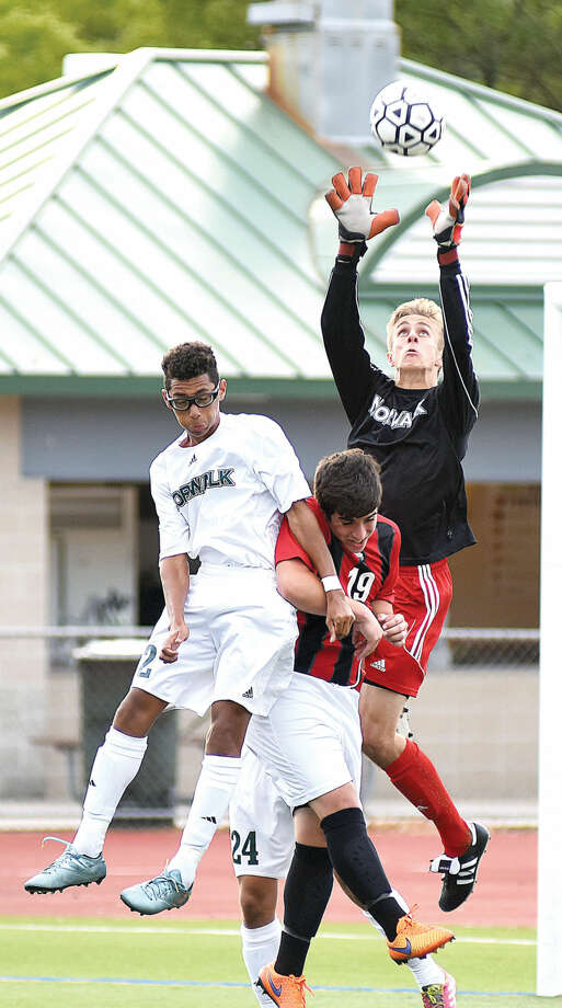 Hour photo/John Nash - Norwalk goalkeeper Tyler Dalton, right, outleaps teammate Michael Hidalgo, left, and Bridgeport Central's Fillipe Dias to come up with the ball on a direct kick in the second half of Tuesday's FCIAC boys soccer game at Testa Field in Norwalk.