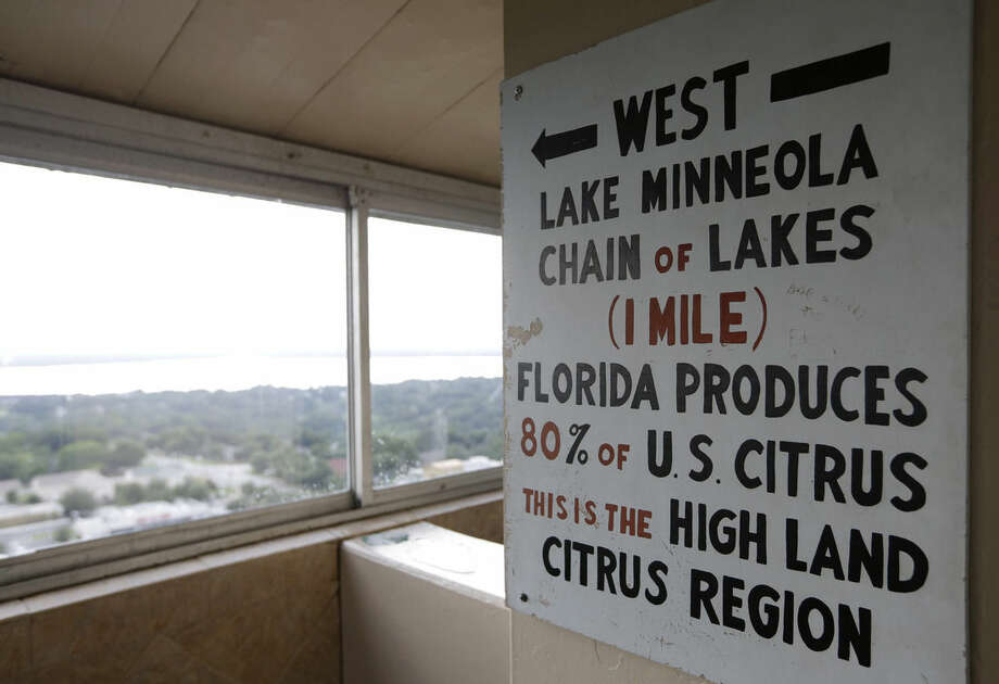 In this Friday, July 25, 2014 photo, a sign in the Florida Citrus Tower points west to Florida's citrus growing region, in Clermont, Fla. The observation tower was built in 1956 as a tourist attraction to view miles of citrus groves. Today Florida's $9 billion citrus industry is facing its biggest threat yet by a tiny invasive bug called the Asian Citrus Psyllid, which carries bacteria that are left behind when the psyllid feeds on a citrus tree's leaves. Eventually disease clogs the tree's vascular system and the tree slowly dies. (AP Photo/Lynne Sladky