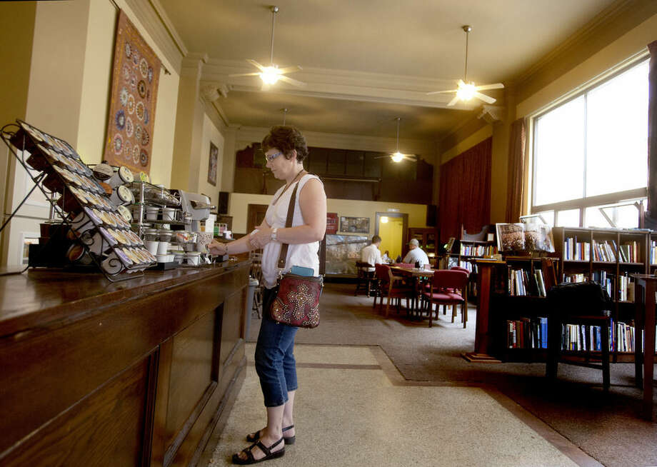 In an Aug. 22, 2014 photo, Kay King of Wahpeton, N.D., stops in for coffee at 'The Vault', a self-serve coffee shop in downtown Valley City, N.D. According to owner David Brekke, small-town living is what allows the North Dakota coffee shop to operate on the honor system. (AP Photo/Bruce Crummy)