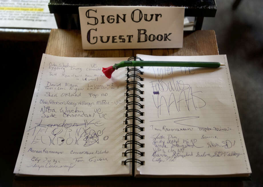 An Aug. 22, 2014 photo shows the guest book, a popular feature at 'The Vault', a self-serve coffee shop in downtown Valley City, North Dakota., According to owner David Brekke, small-town living is what allows the North Dakota coffee shop to operate on the honor system. (AP Photo/Bruce Crummy)