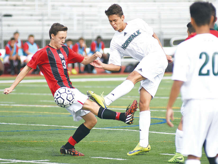 Hour photo/John Nash - Norwalk's Santiago Mesa, center, looks to get off a shot as Bridgeport Central defender Victor Pieriera interferes during the first half of Tuesday's FCIAC boys soccer game at Testa Field in Norwalk.