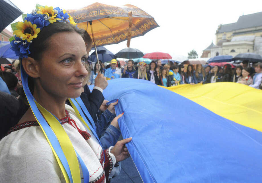 Ukrainians living in Poland hold their national flag during celebrations marking the 23. anniversary of Ukraine's independence, in Warsaw, Poland, Sunday, Aug. 24, 2014. (AP Photo/Alik Keplicz)