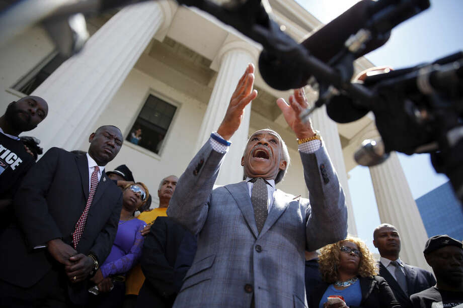 FILE - In this Aug. 12, 2014 file photo civil rights activist Rev. Al Sharpton speaks during a news conference with Michael Brown Sr., left, Brown family attorney Benjamin Crump, second from left, and Lesley McSpadden, Brown's mother, on Crump's right, in St. Louis. Sharpton, who has parachuted into racially-charged crises for more than three decades, returns to Ferguson on Monday, Aug. 25, 2014, to speak at the funeral for Michael Brown, cementing his place at the intersection of advocacy and controversy. (AP Photo/Jeff Roberson, File)