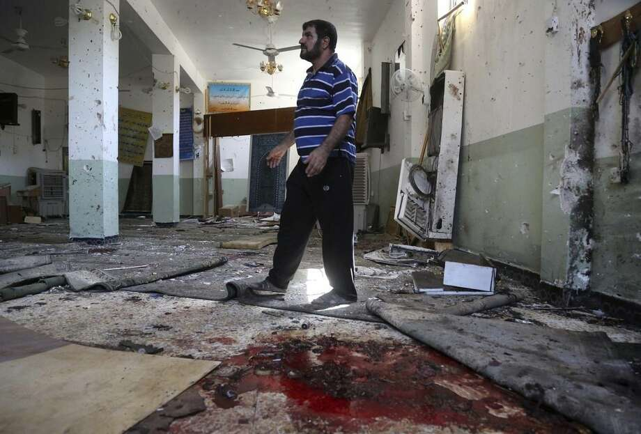 A man walks past blood stains on the floor of the Imam Ali mosque after a suicide bomb attack in New Baghdad, Iraq, Monday, Aug. 25, 2014. Iraqi officials say a wave of attacks targeting commercial areas in and outside Baghdad has killed and wounded scores of people. They say the deadliest of Monday's bombings was carried out by a suicide bomber who blew up himself among Shiite worshippers who were leaving Imam Ali mosque after noon prayers in the capital's eastern New Baghdad area, killing over a dozen people and wounding many others. (AP Photo/ Khalid Mohammed)