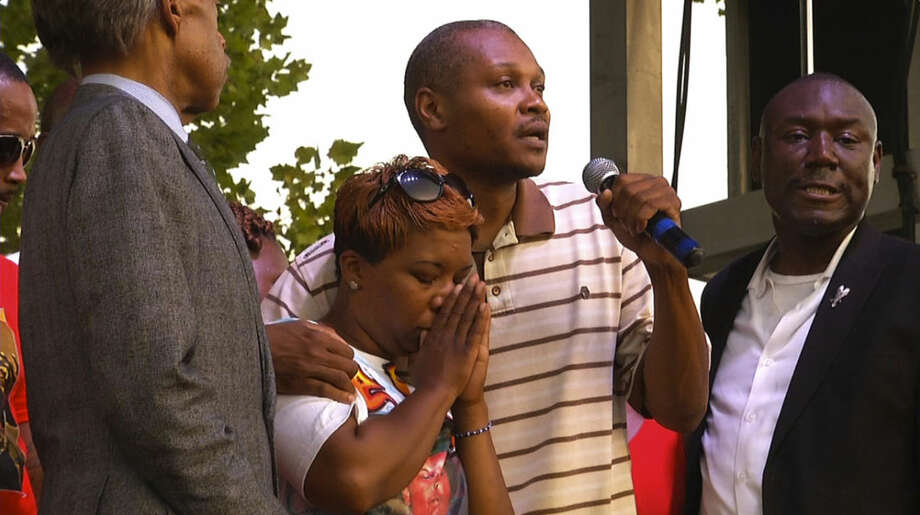 Lesley McSpadden, Michael Brown's mother, second from left, stands next to her cousin, Eric Davis, as he addresses the crowd at Peace Fest, Sunday, Aug. 24, 2014, in St. Louis. Hundreds of people gathered in St. Louis' largest city park Sunday at a festival that promoted peace over violence. (AP Photo/Alex Sanz)