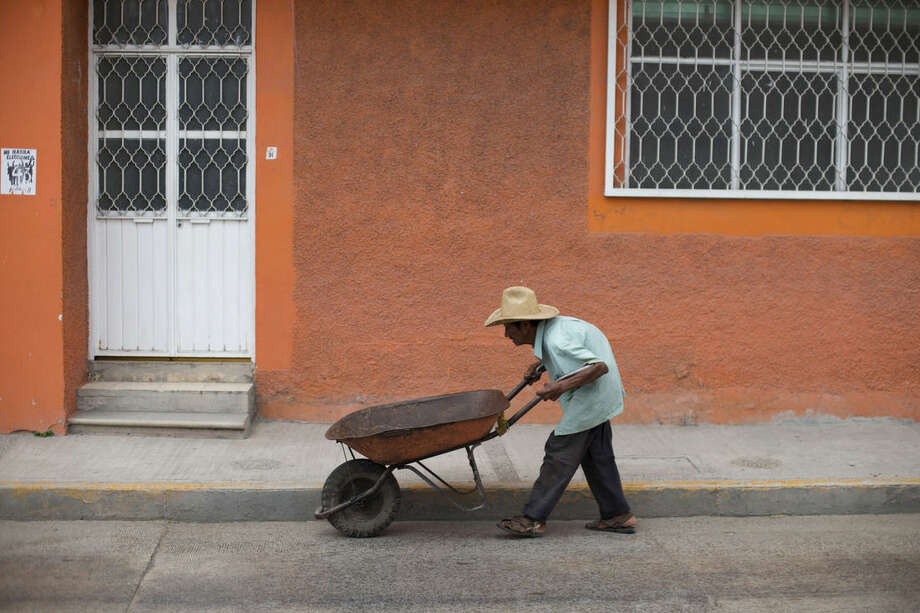 An elderly man pushes a wheelbarrow along a street in Tixtla, in Mexico's southern Guerrero State, Friday, Sept. 25, 2015. Saturday will mark one year since the disappearance of 43 student teachers from the Rural Normal School of Ayotzinapa, located in Tixtla. Mexico's normal school were created to train students from impoverished rural communities to be teachers. (AP Photo/Rebecca Blackwell)