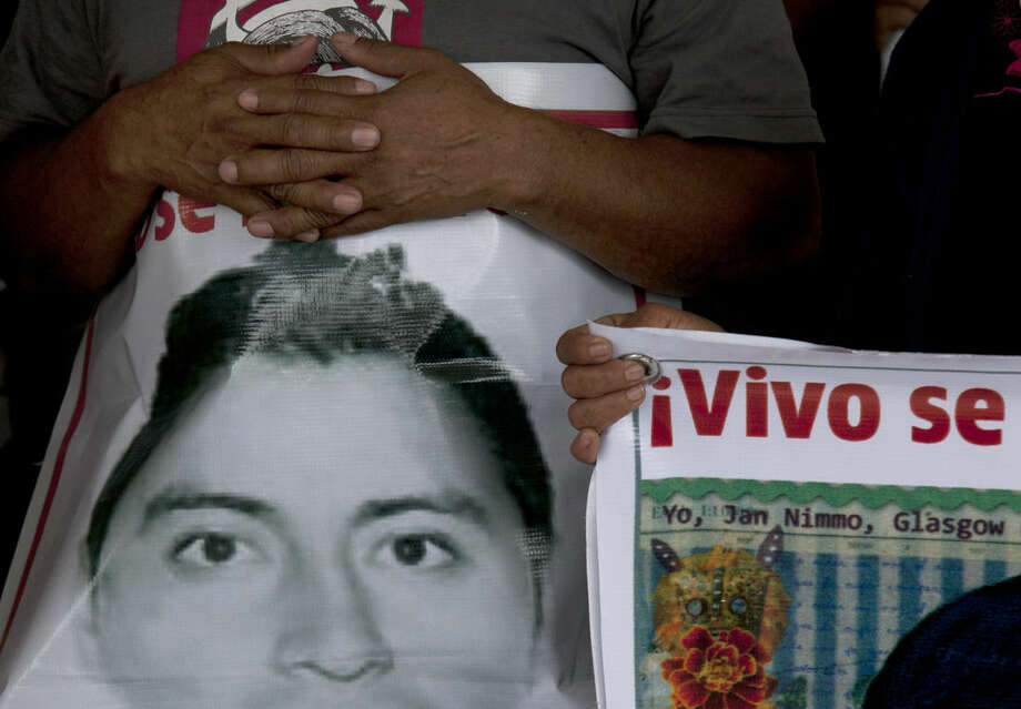 The relative of one of the 43 missing college students holds an image of his missing loved one during a press conference at the end of the relatives' 43 hour protest fast in the Zocalo, Mexico City's main square, Friday, Sept. 25, 2015, one day before the one year anniversary of the students' disappearance. According to an independent group of experts, their disappearances, and the killings of six others on Sept. 26, 2014, were the result of a long, coordinated attack against students from the Raul Isidro Burgos Rural Normal School of Ayotzinapa. (AP Photo/Marco Ugarte)