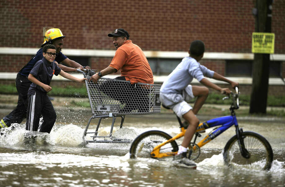 FILE - In this Thursday, June 18, 2015, file photo, a man is brought across a flooded parking lot in a shopping cart in Philadelphia after a water main rupture in the city's Hunting Park section. The Philadelphia water department, the nation's oldest, is spending millions of dollars per year to replace its worst pipes. (AP Photo/Matt Rourke)