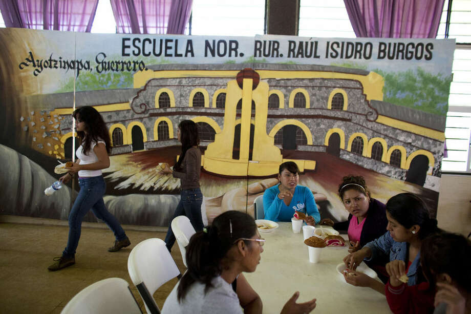 Students from the Rural Normal School of Tlaxcala who have come to support the students of the Rural Normal School of Ayotzinapa eat breakfast inside the school cafeteria, in front of a picture of the school, in Tixtla, Guerrero State, Saturday, Sept. 26, 2015. Protest marches to mark the one year anniversary of the disappearance of 43 student teachers were planned for Saturday afternoon in Mexico City and multiple towns in Guerrero.(AP Photo/Rebecca Blackwell)