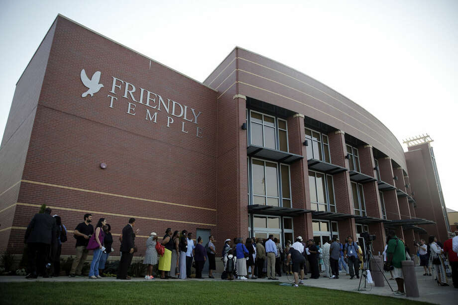 People begin to line up to attend the funeral for Michael Brown, Monday, Aug. 25, 2014, in St. Louis. Brown, who is black, was unarmed when he was shot Aug. 9 by Officer Darren Wilson, who is white. A grand jury is considering evidence in the case and a federal investigation is also underway. (AP Photo/Jeff Roberson)
