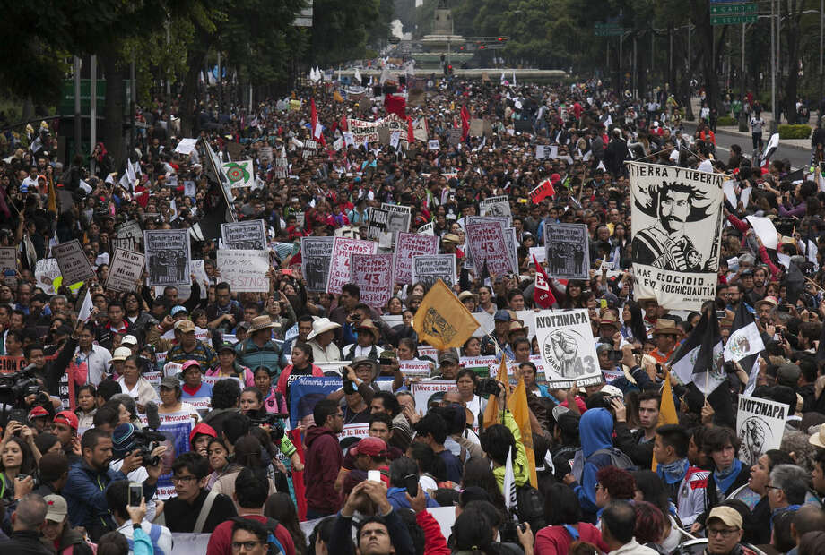 Thousands gather to mark the one-year anniversary of the disappearance of 43 students with a march in Mexico City, Saturday, Sept. 26, 2015. One year ago, several students and bystanders were killed and 43 students vanished in the town of Iguala, allegedly taken by police and then handed over to a criminal gang who burned their bodies in a garbage dump, according to a federal investigation. Families of the missing and independent investigators cast doubts on the official version. (AP Photo/Marco Ugarte)