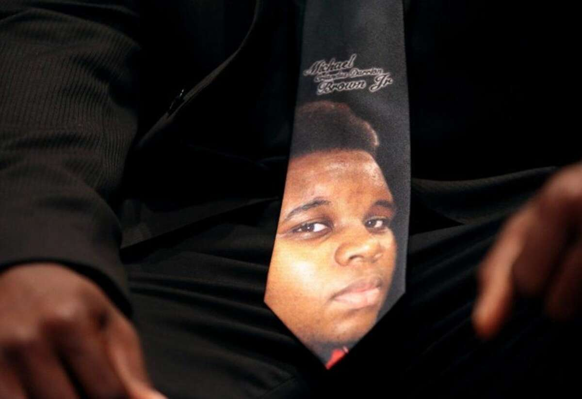 """FILE - In this Aug. 25, 2014, file photo, a man wears a tie decorated with a picture of Michael Brown during Brown's funeral at Friendly Temple Missionary Baptist Church in St. Louis. Six months after 18-year-old Michael Brown died in the street in Ferguson, Missouri, the Justice Department is close to announcing its findings in the racially charged police shooting that launched """"hands up, don't shoot"""" protests across the nation. (AP Photo/St. Louis Post Dispatch, Robert Cohen, Pool)"""
