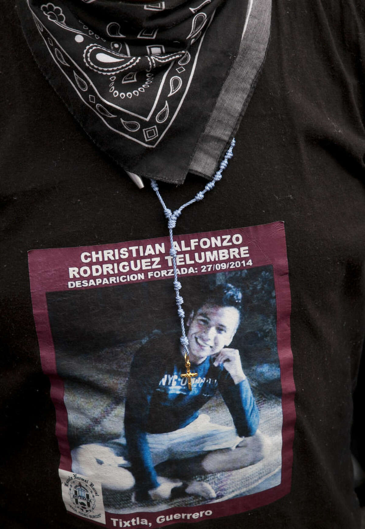 Clemente Rodriguez wears a photo of his missing son Christian Rodriguez Telumbre at the end of a 43 hour protest fast in the Zocalo, Mexico City's main square, Friday, Sept. 25, 2015, the day before the one year anniversary of the disappearance of 43 rural college students in Guerrero state. According to an independent group of experts, their disappearances, and the killings of six others on Sept. 26, 2014, were the result of a long, coordinated attack against students from the Raul Isidro Burgos Rural Normal School of Ayotzinapa. (AP Photo/Marco Ugarte)