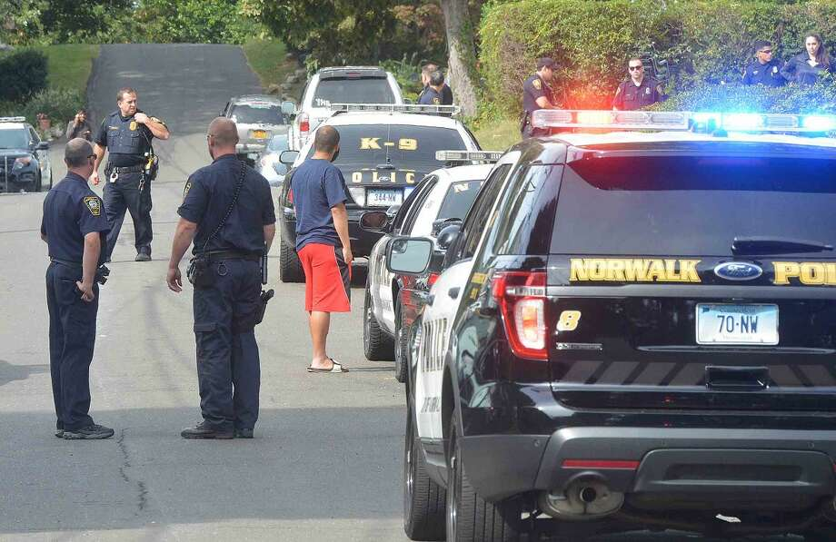 Hour photo/Alex von KleydorffNorwalk Police block off Adamson Avenue on Friday morning after a neighbor shot a paintball gun at another neighbor's home.