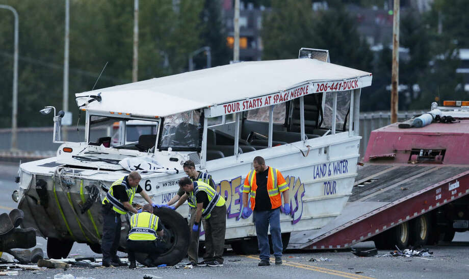 "Seattle Police officers photograph the front tire and wheel of a ""Ride the Ducks"" tourist vehicle before the bus is loaded onto a flatbed tow truck Thursday, Sept. 24, 2015, after it was involved in a fatal crash with a charter passenger bus earlier in the day in Seattle. (AP Photo/Ted S. Warren)"